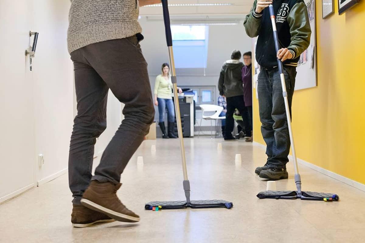 Nuoria moppaamassa lattiaa.