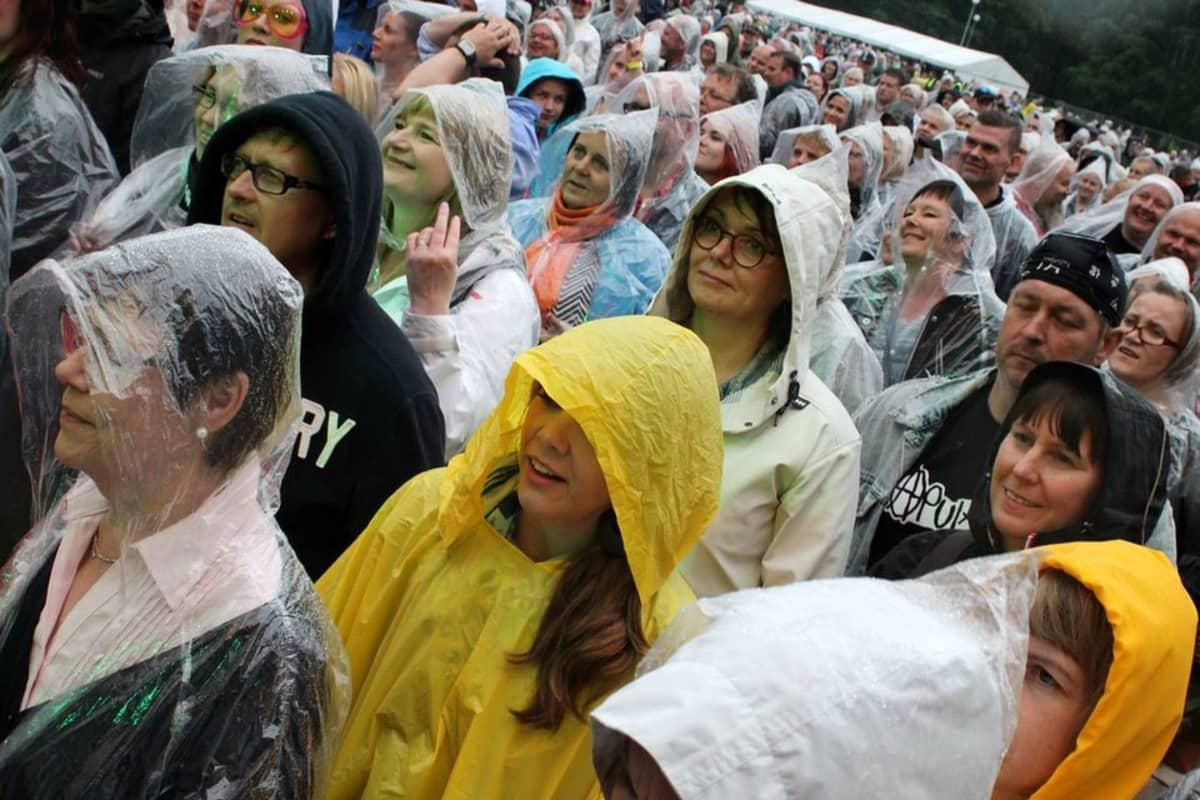 Ihmiset hymyilevät sadetakeissaan