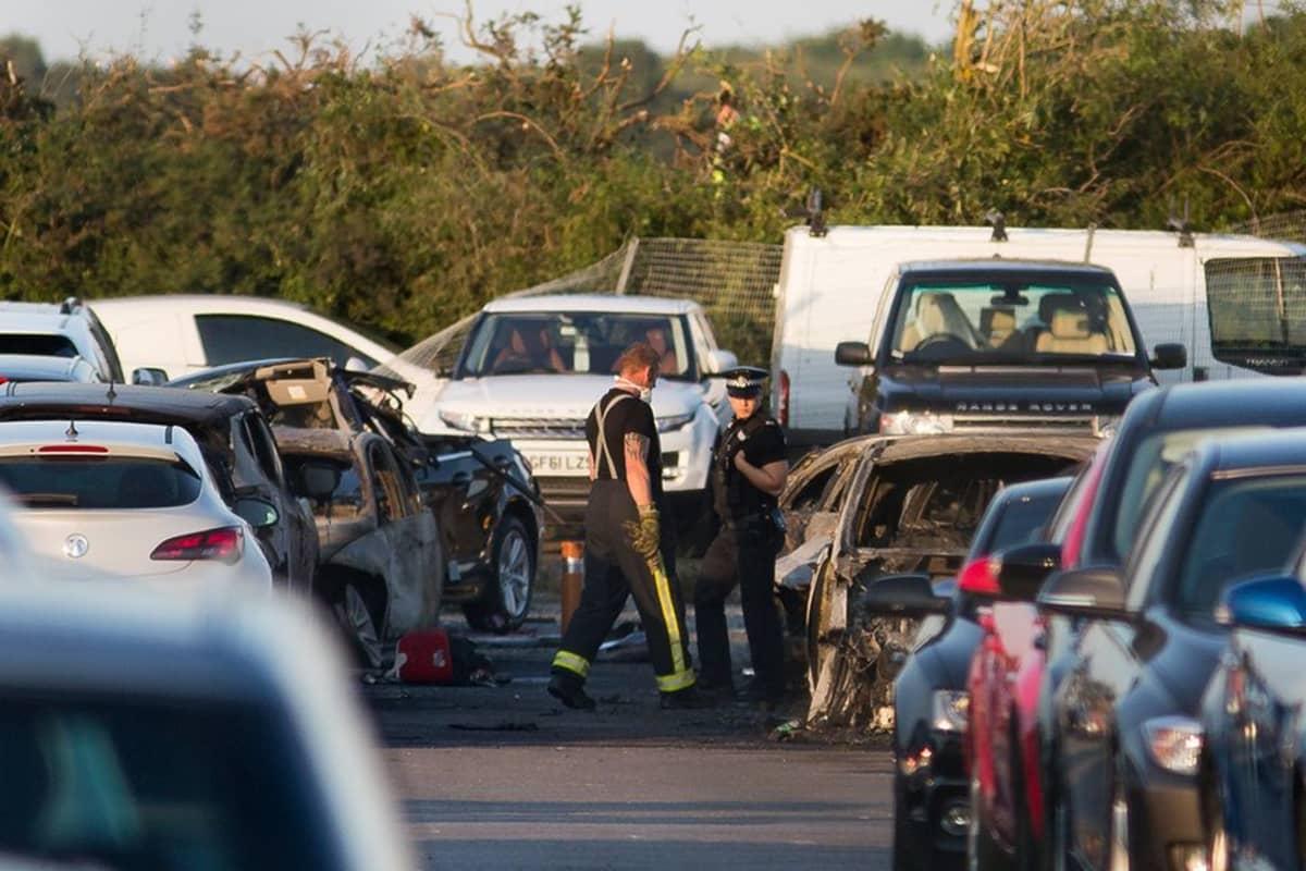 Viranomaisia palaneiden autojen keskellä.