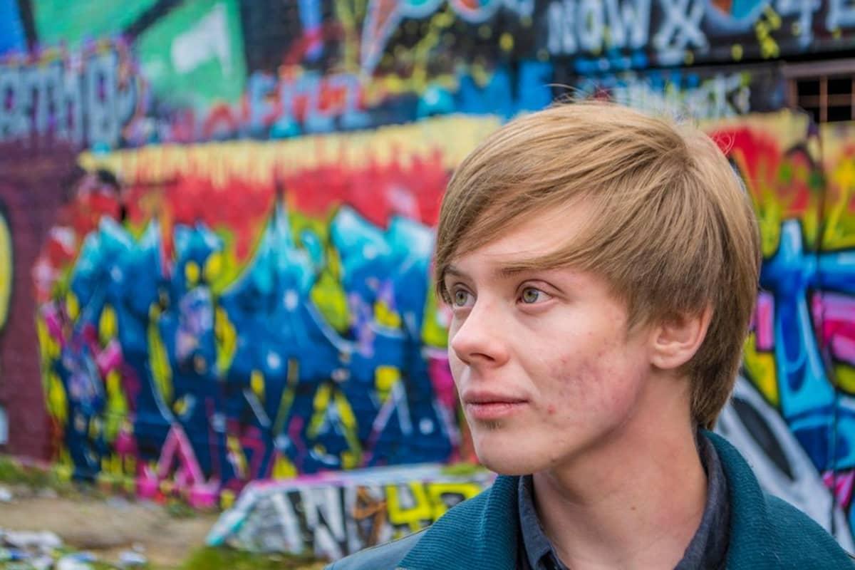 Mies seisoo graffitiseinän edessä.