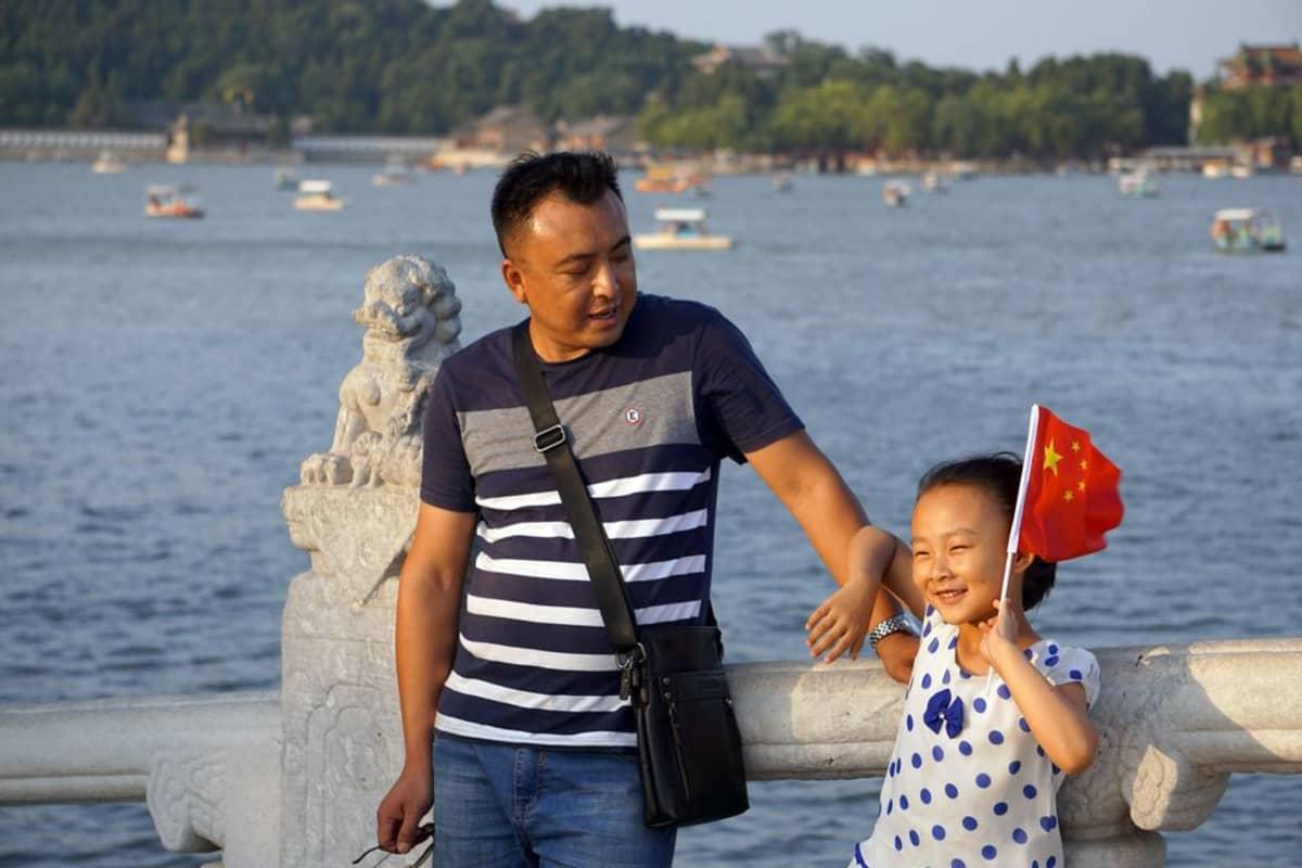 Kiinalainen isä ja tytär, joka heiluttaa Kiinan lippua.