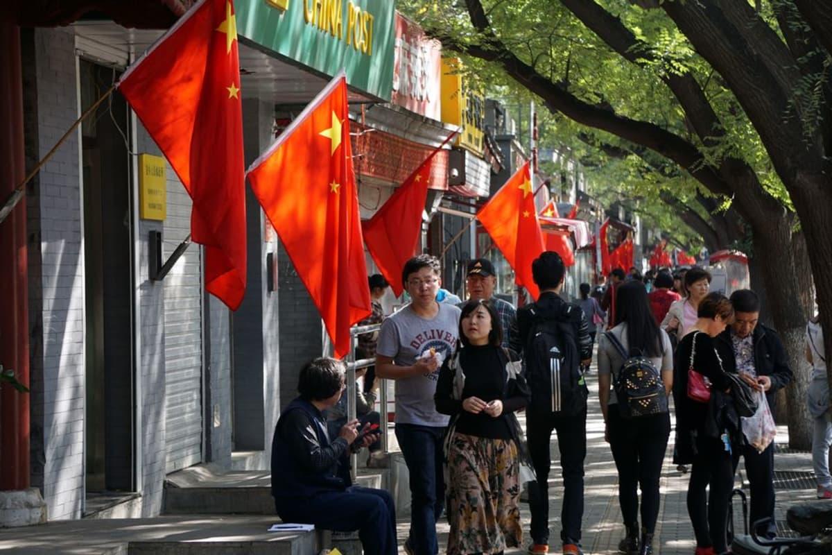 Kiinan lippuja pekingiläisten kauppojen edustalla.