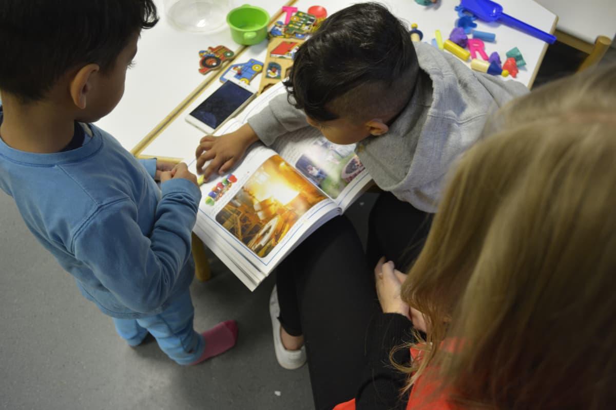 Turvapaikanhakijoiden lapset lukevat kirjaa Hennalassa.