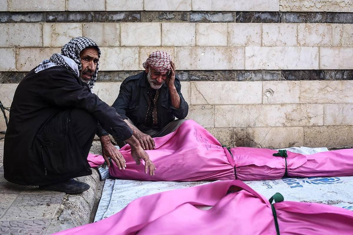 Kaksi syyrialaismiestä ilma-iskussa kuolleiden omaistensa ruumiiden äärellä.