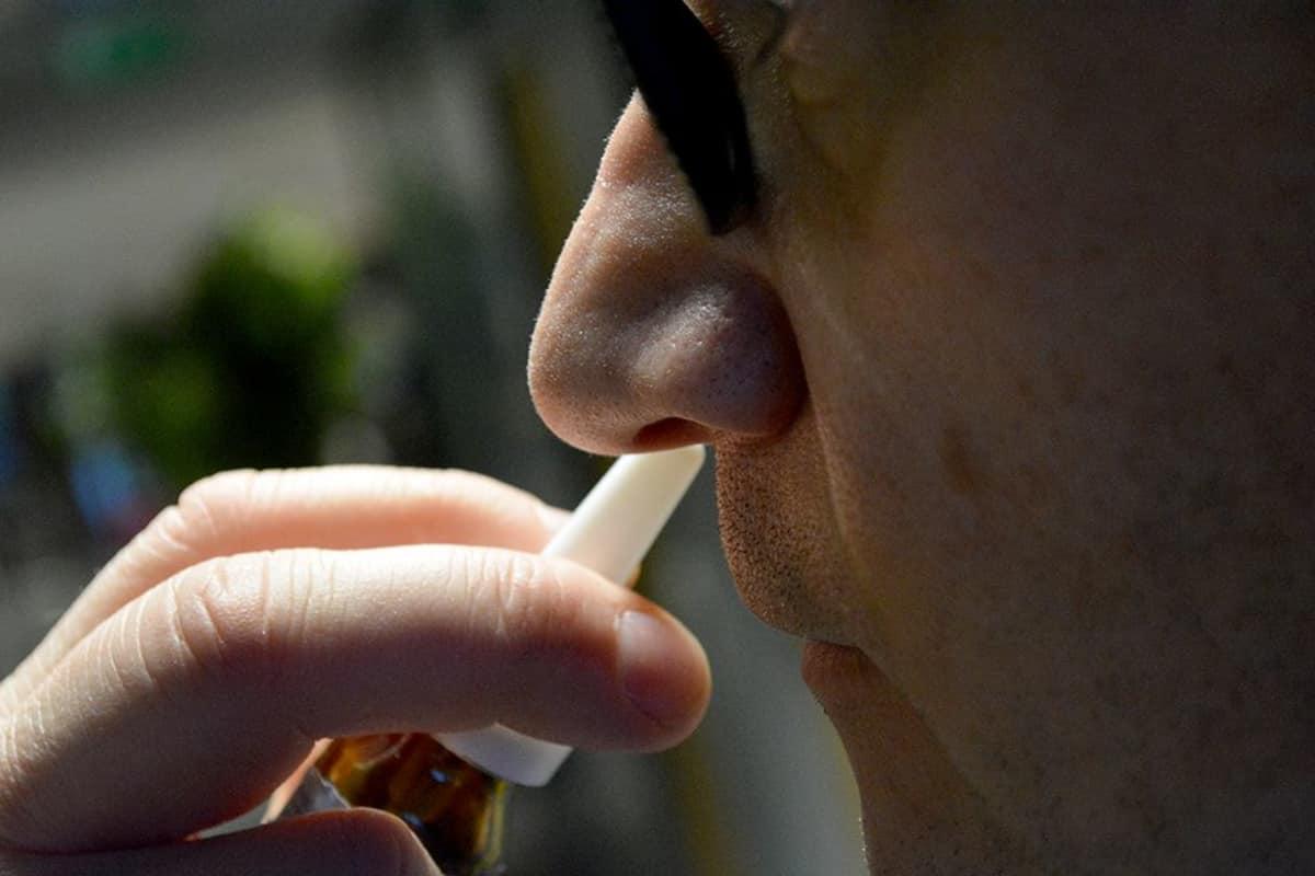 Mies suihkauttaa nenäsumutetta nenäänsä