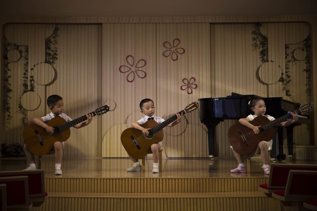 Pohjois-Korean nuoret kitaristit esittelevät taitojaan pjongjangilaisessa lastentarhassa.