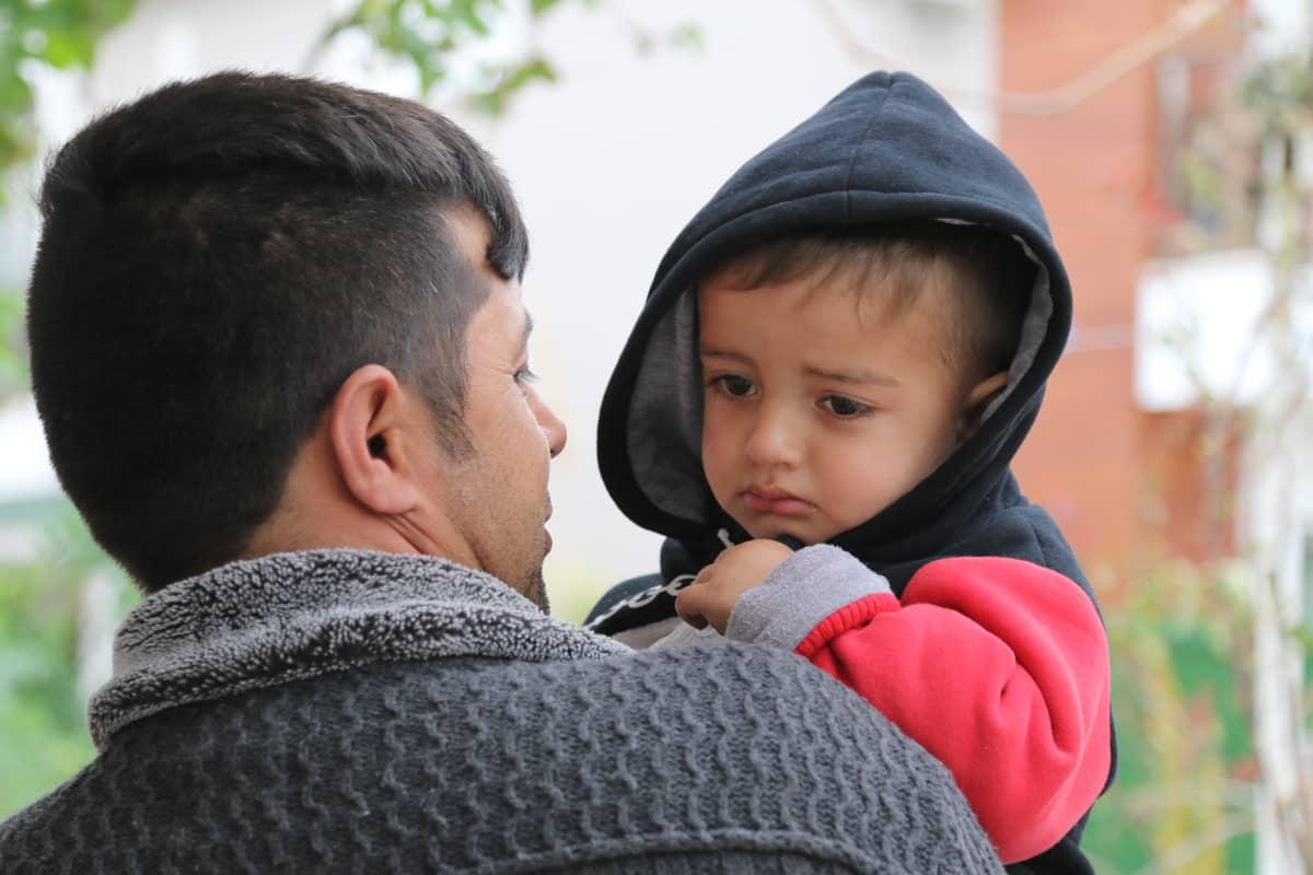 Surullinen lapsi katselee isäänsä.