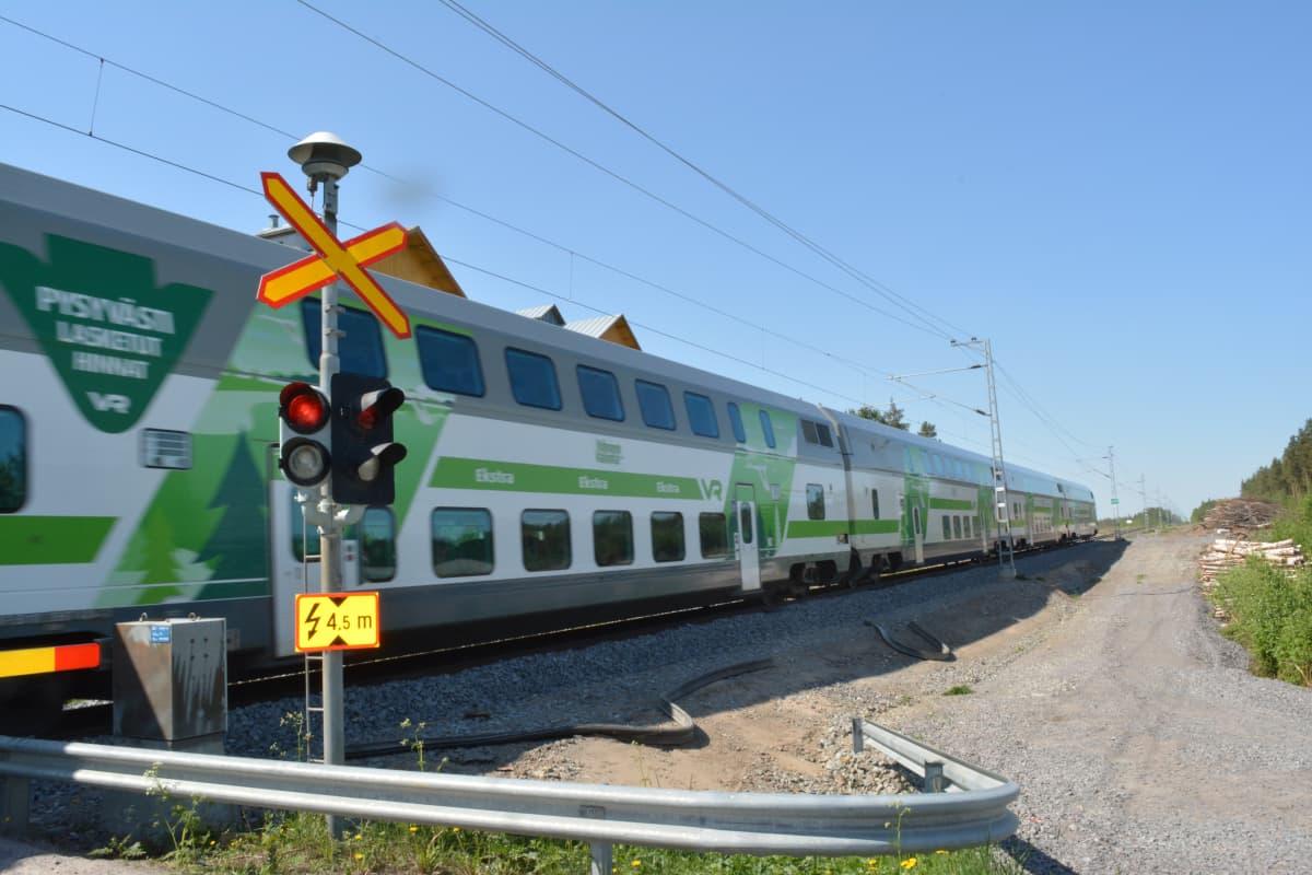 Juna ohittaa tasoristeyksen lähellä Ylistaron asemaa