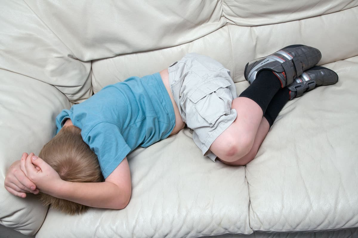 Nuori poika makaa sohvalla.
