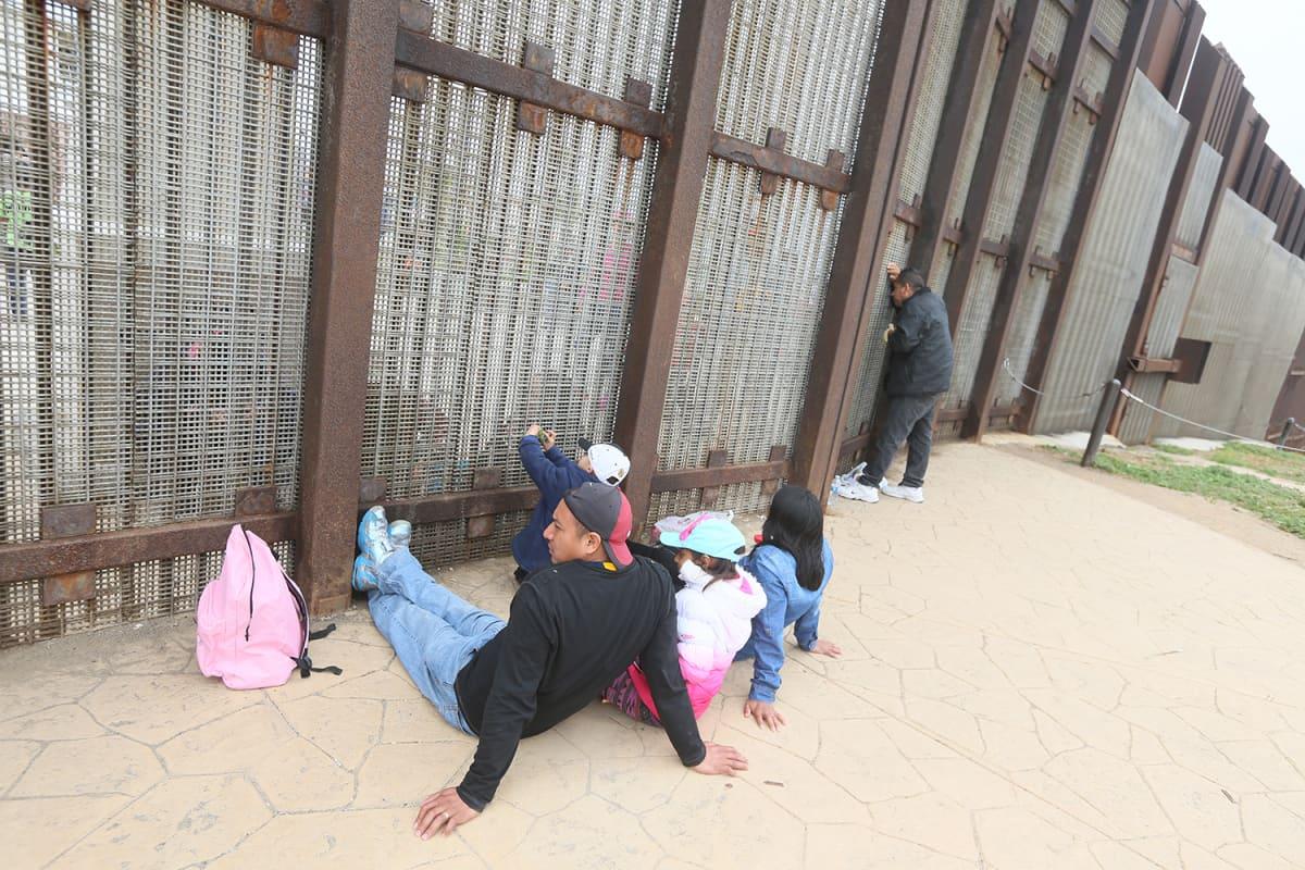 Isä, äiti ja kaksi lasta istuvat maassa Yhdysvaltojen ja Meksikon välisen raja-aidan vierellä.