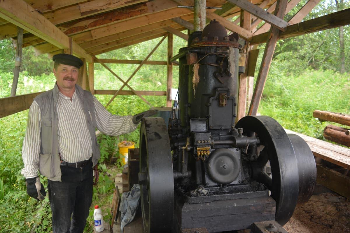 Reijo Kivijärvi sekä hänen kunnostamansa vanha hehkukuulamoottori