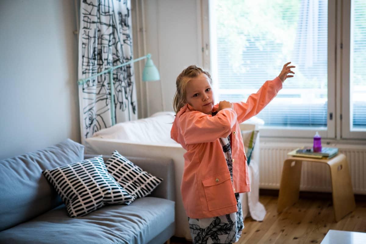 Matilda Salmi aloittaa koulun tänään. Kuvassa hän pukee päälleen kotona.