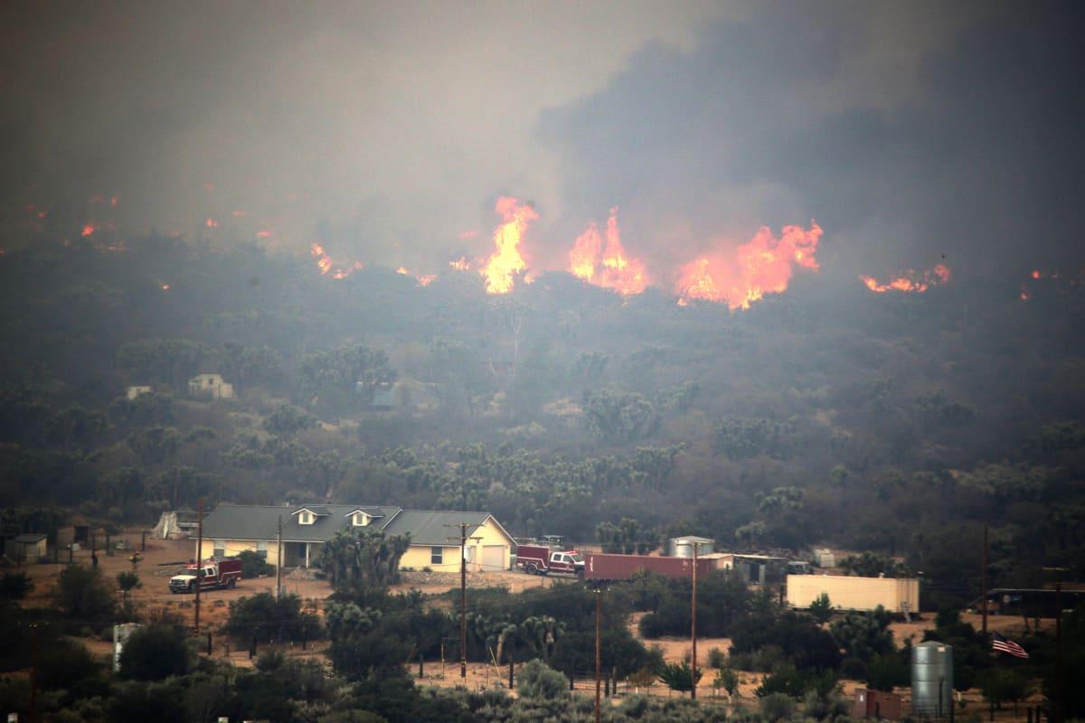 Sammutusyksiköt yrittävät suojella asuinrakennusta Phelanissa, San Bernardinon piirikunnassa 17.8. 2016. Los Angelesin itäpuolella riehuva tulipalo leviää nopealla vauhdilla.
