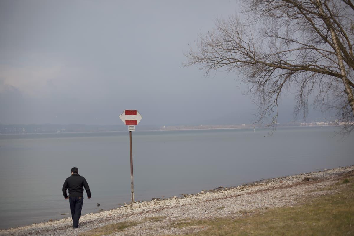Mies rannalla.