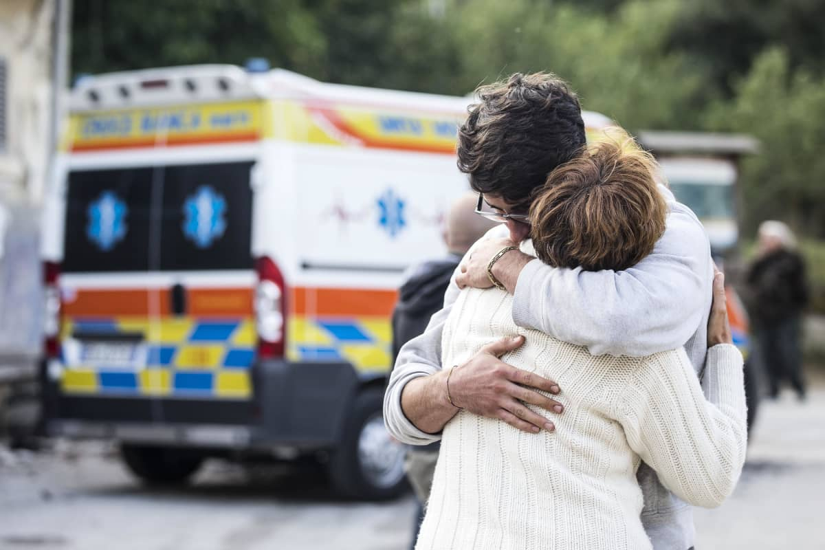Kaksi ihmistä halaa. Taustalla ambulanssi.