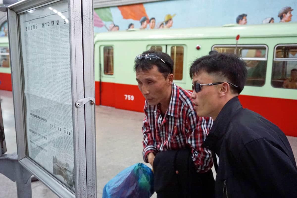 Miehet lukevat sanomalehteä metroasemalla.