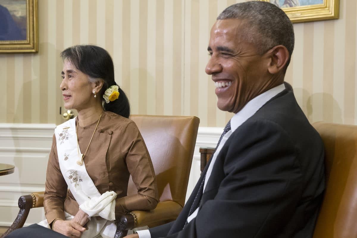 Ruskeaan pukeutuneen naisen mustissa hiusksissa on keltainen kukka, hänen vieressään istuu naurava mies.