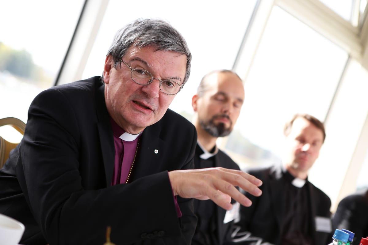 Piispa Kaarlo Kalliala istuu pöydän ääressä ja katsoo kameraan.