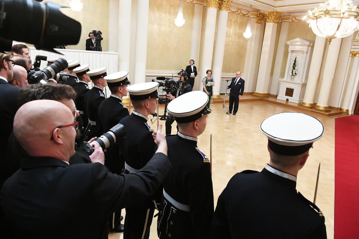 Linnan vieraita on presidenttiparin lisäksi vastassa rivistö kadetteja ja katsomollinen valokuvaajia.
