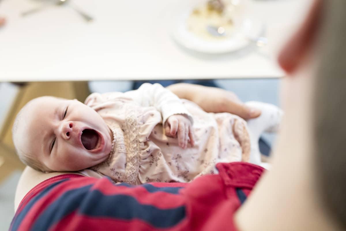 Mies pitää vauvaa sylissä.