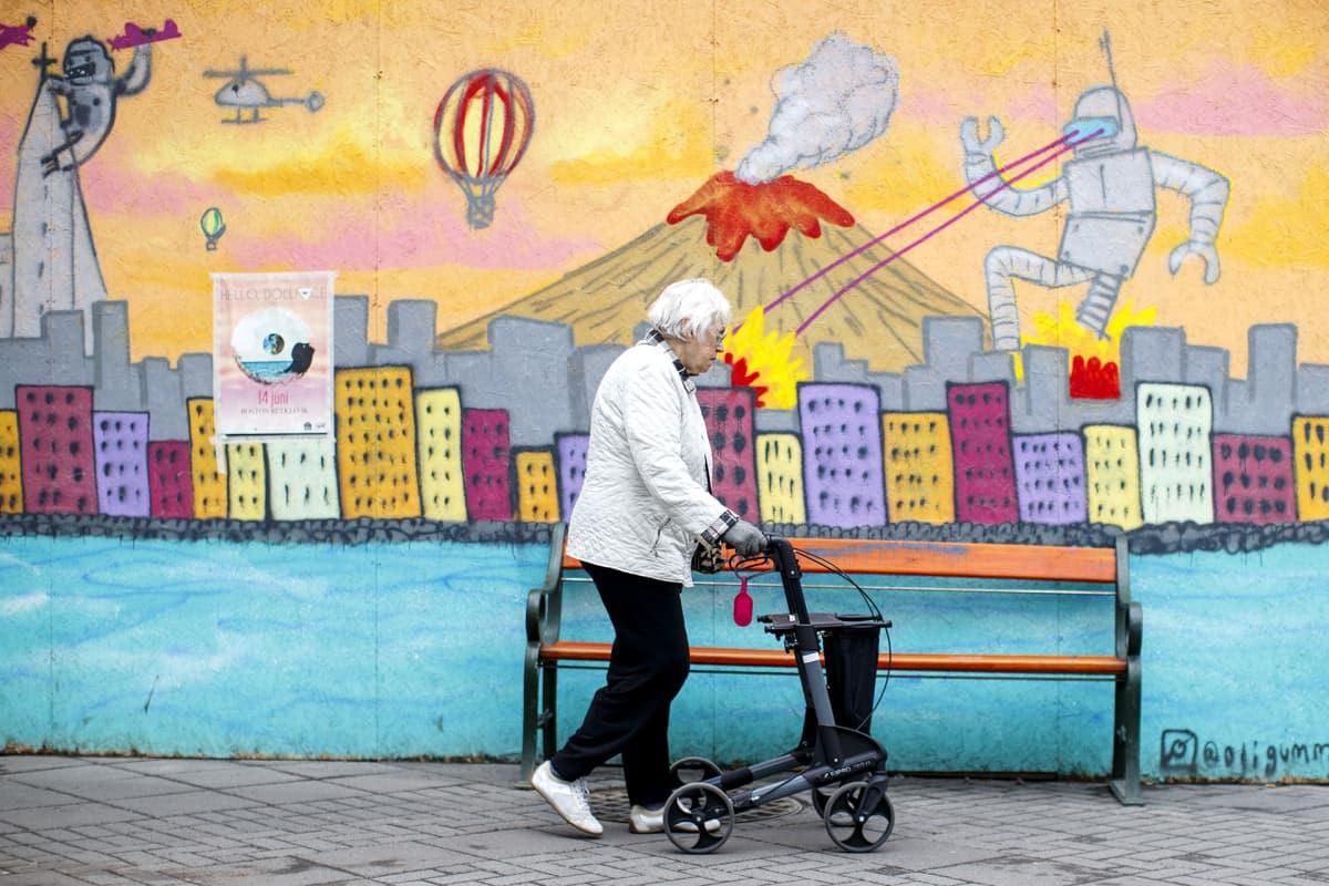 Iäkäs nainen kävelee seinämaalauksen ohitse.