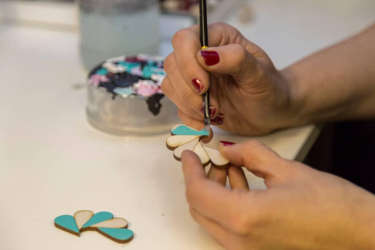 Nina Jatuli maalaa korvakoruja työhuoneellaan.