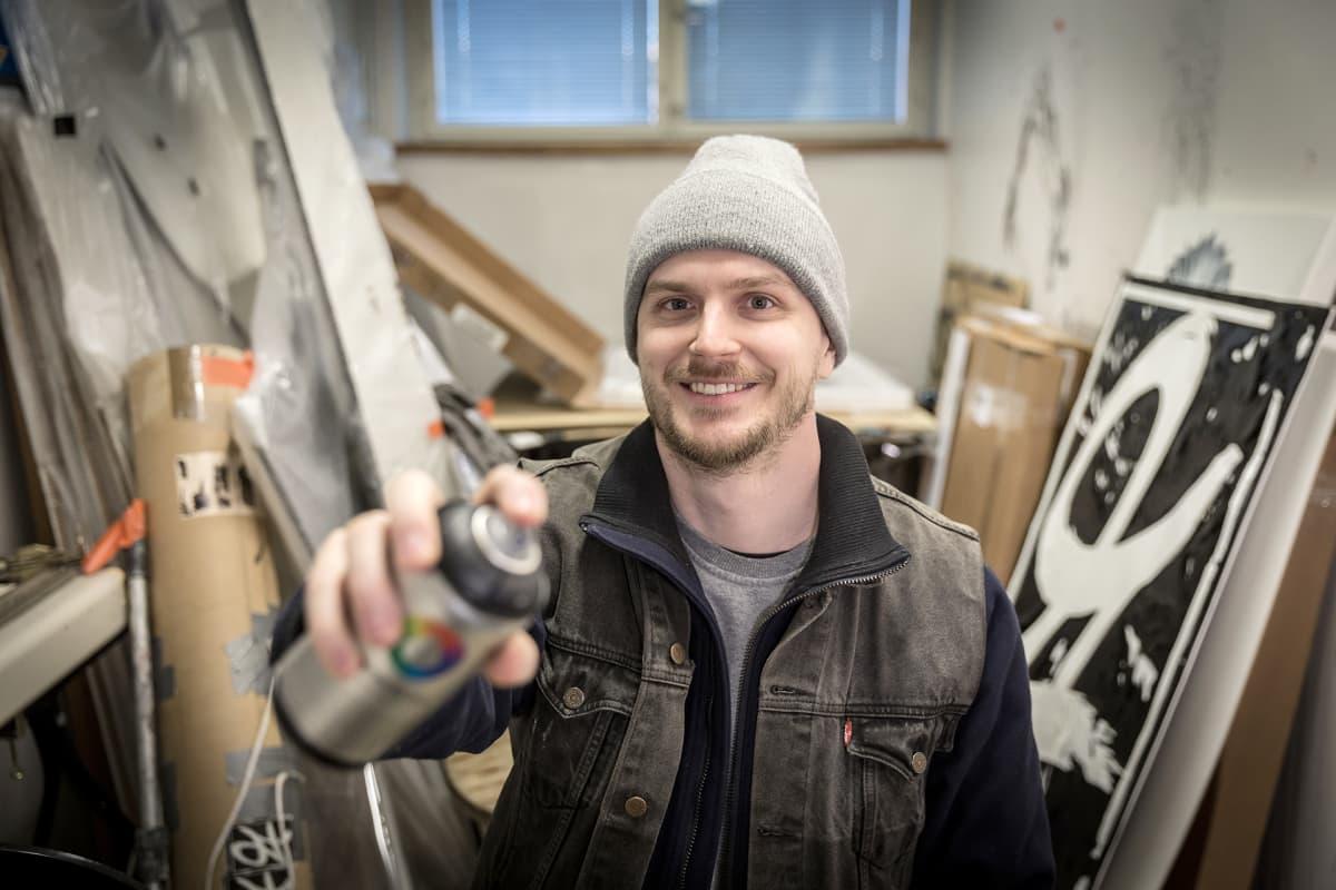 mies ateljeessa spraypullon kanssa
