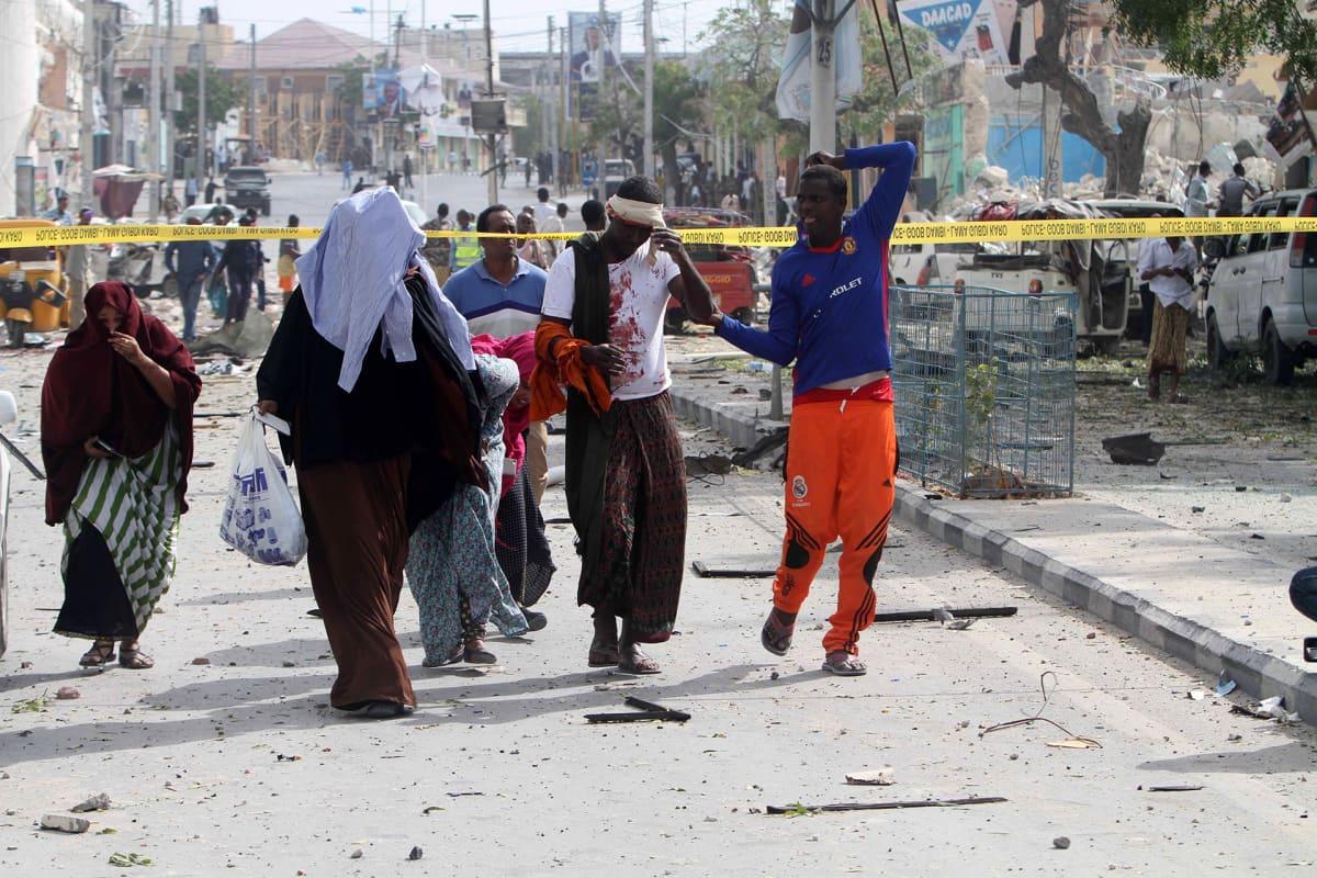 Haavoittuneita ihmisiä kävelee kadulla.
