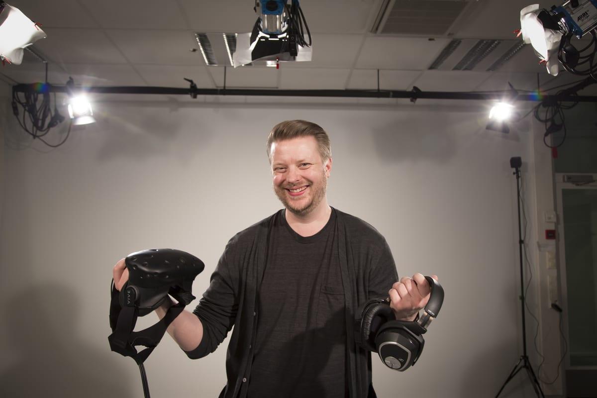 Mies poseeraa studiossa virtuaalilasit ja kuulokkeet kädessä.