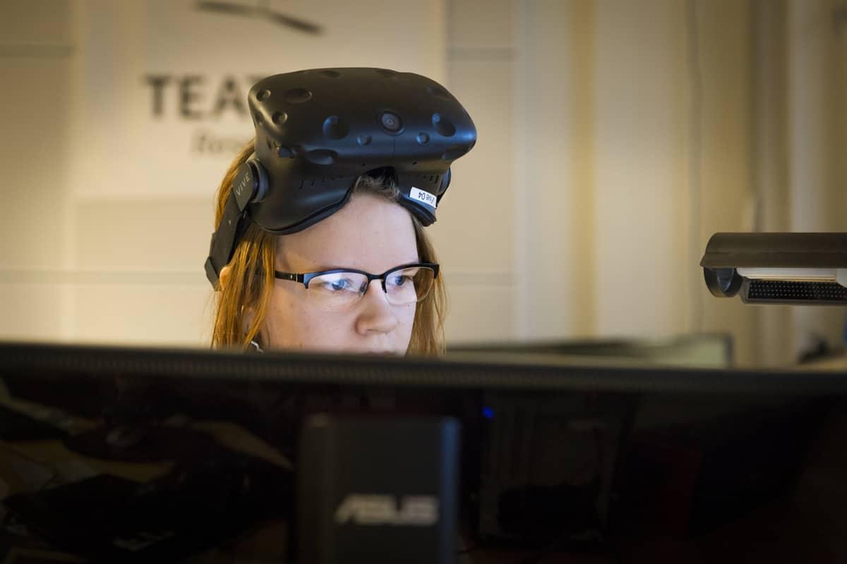 Naine virtuaalilasit otsalla tietokoneen ääressä.