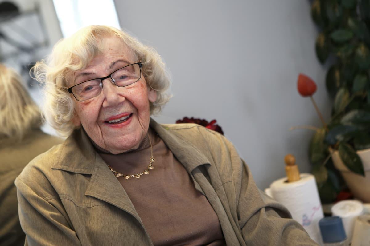 Vanha nainen hymyilee kameralle.