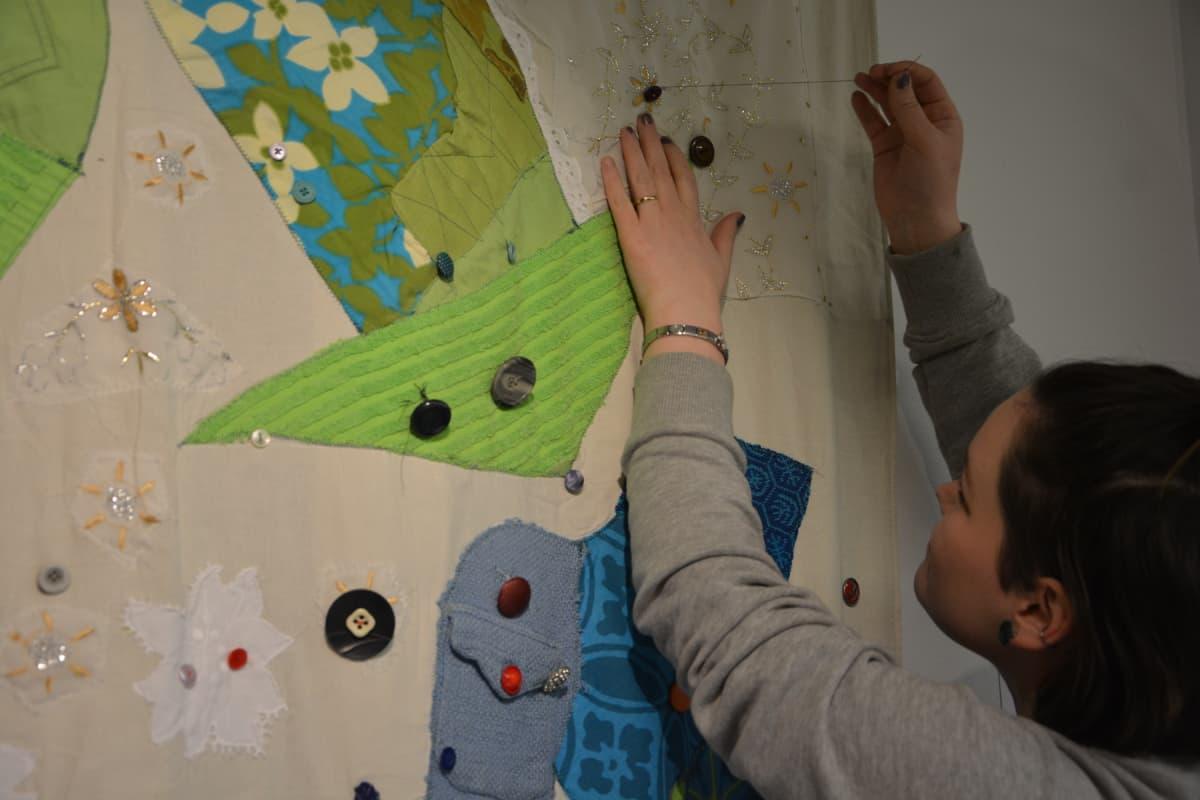nainen ompelee nappia seinävaatteeseen