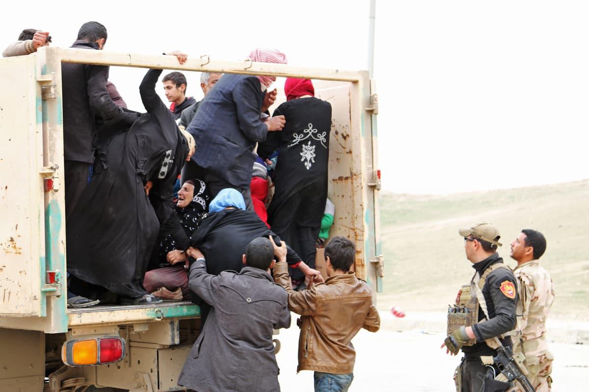 Pakolaisia auton lavalla.