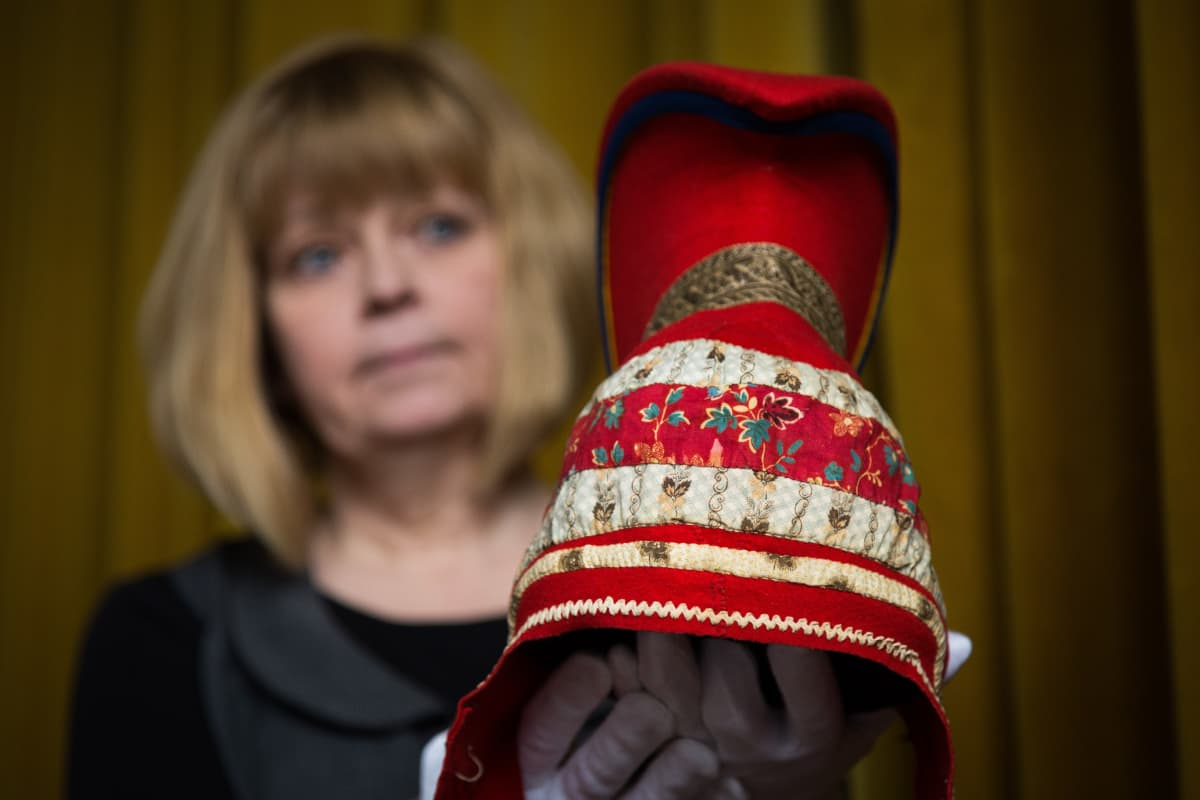 Kansallismuseon intendentti Raila Kataja pitelee kädessään saamelaista sarvilakkia.