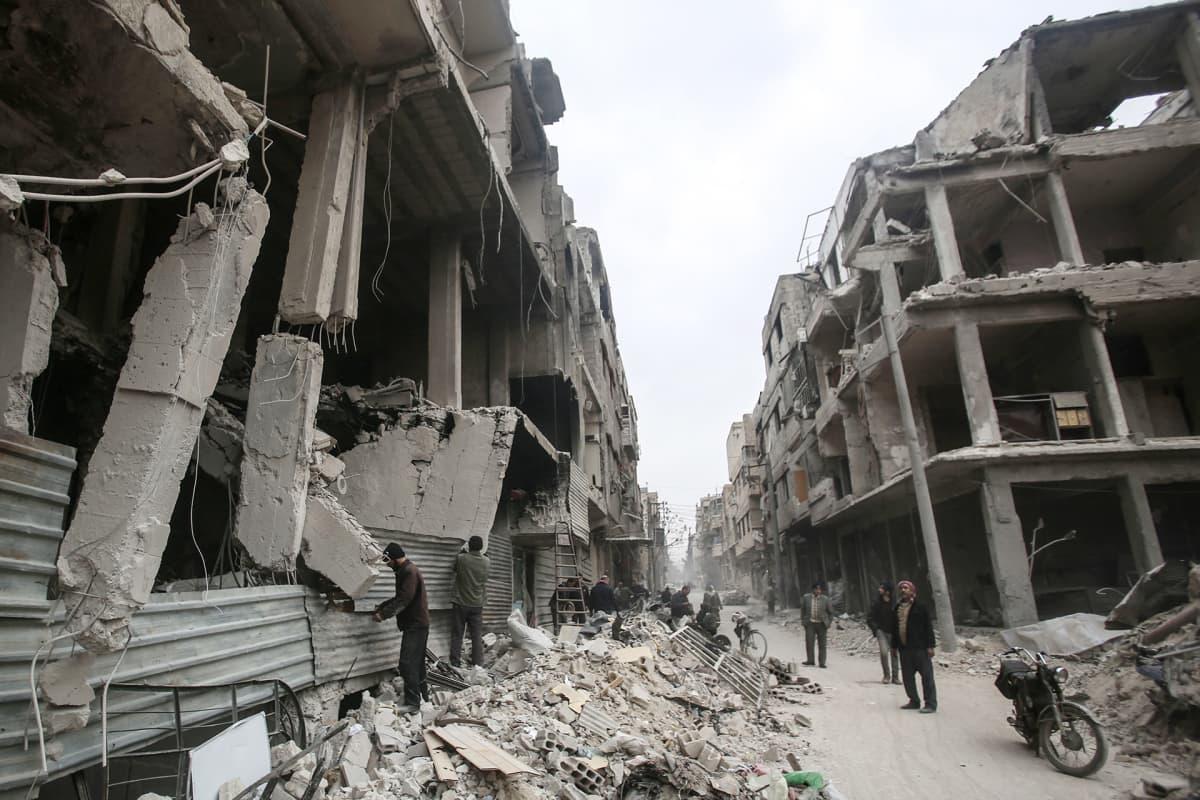 Ihmisiä tuhoutuneiden talojen keskellä Dumassa, helmikuussa.