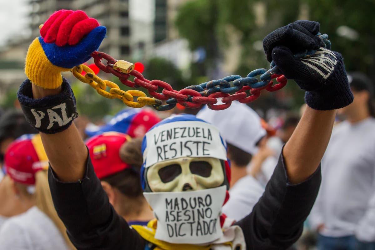 Venezuelan hallituksen vastustajat (kuvassa) ja kannattajat marssivat vappupäivänä 1.5. 2017 pääkaupungin Caracasin kaduilla.