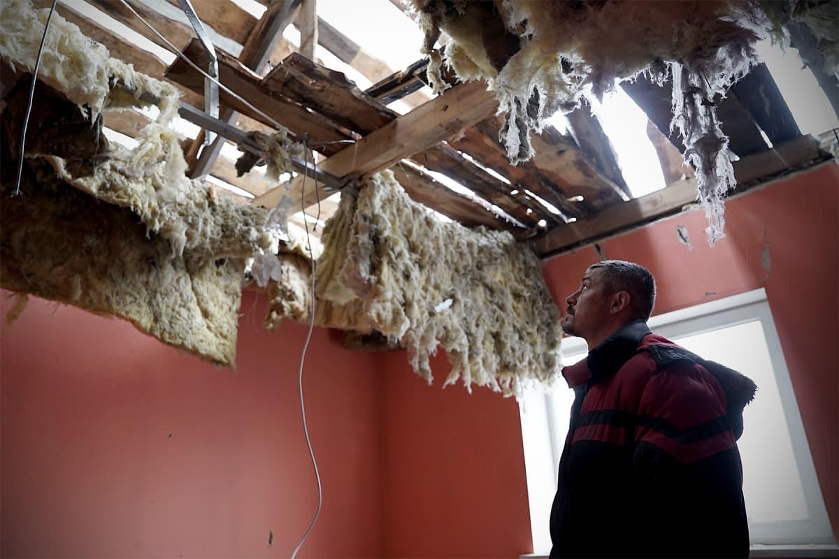 Mies tuhoutuneessa talossaan.