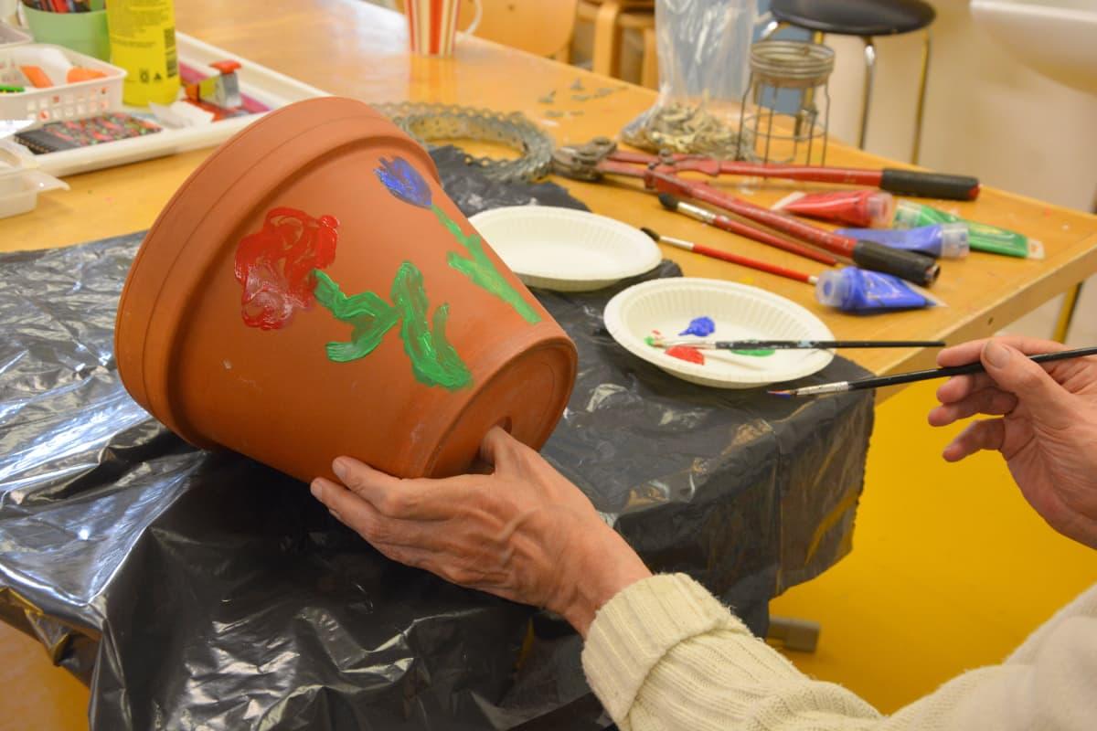 miehen kädet, jotka maalaavat kukkaruukkua