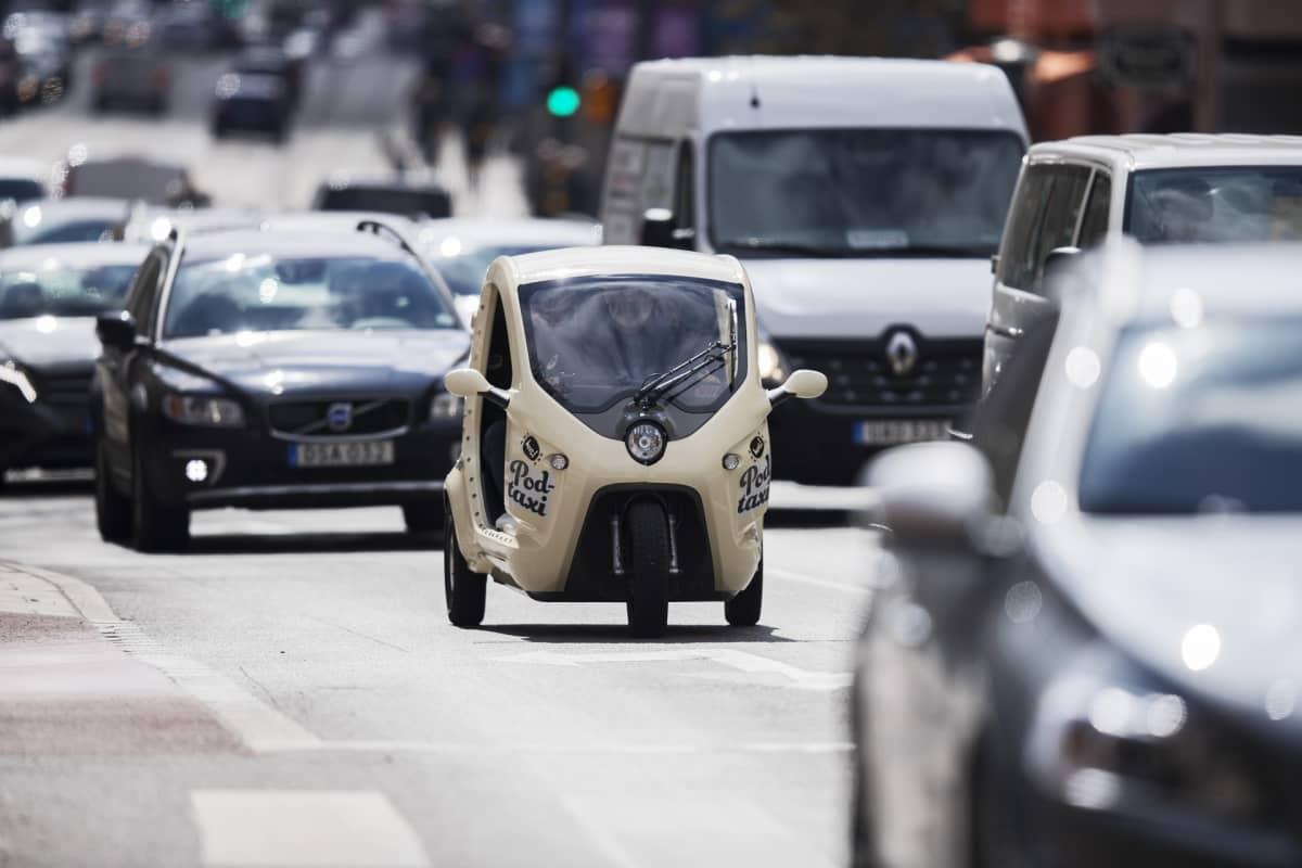 Valkoinen kolmipyöräinen mopeditaksi ajaa autojen keskellä Tukholmassa.