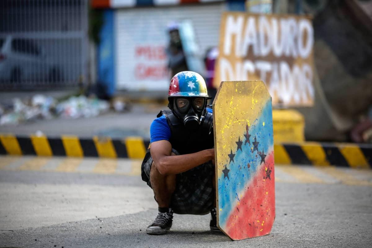Mielenosoittaja on suojautunut kilven taakse happinaamari päässään.