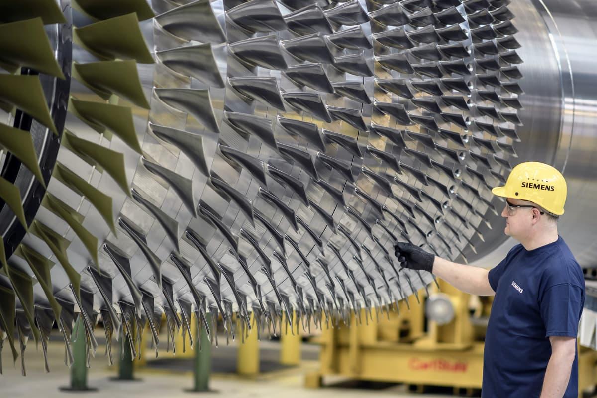 Siemensin työntekijä seisoo suuren turbiinin vieressä tehtaalla Berliinissä.