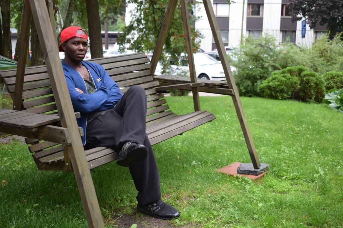 tummaihoinen mies istuu mietteliäänä keinussa