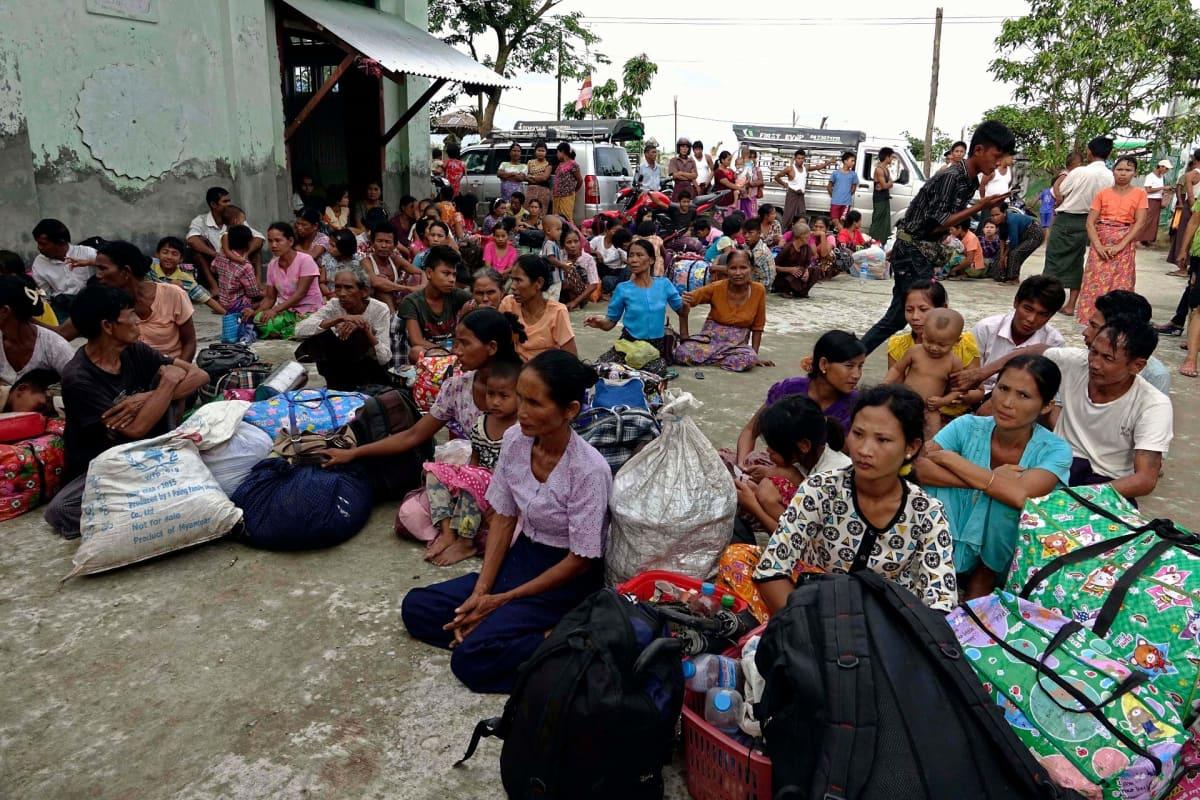 Naisia ja lapsia istuu maassa laukkujen ja kassien kanssa.