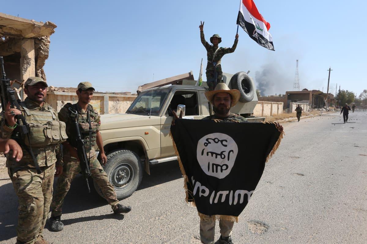 Irakilaissotilaita. Etualalla seisova sotilas esittelee Isisin lippua.