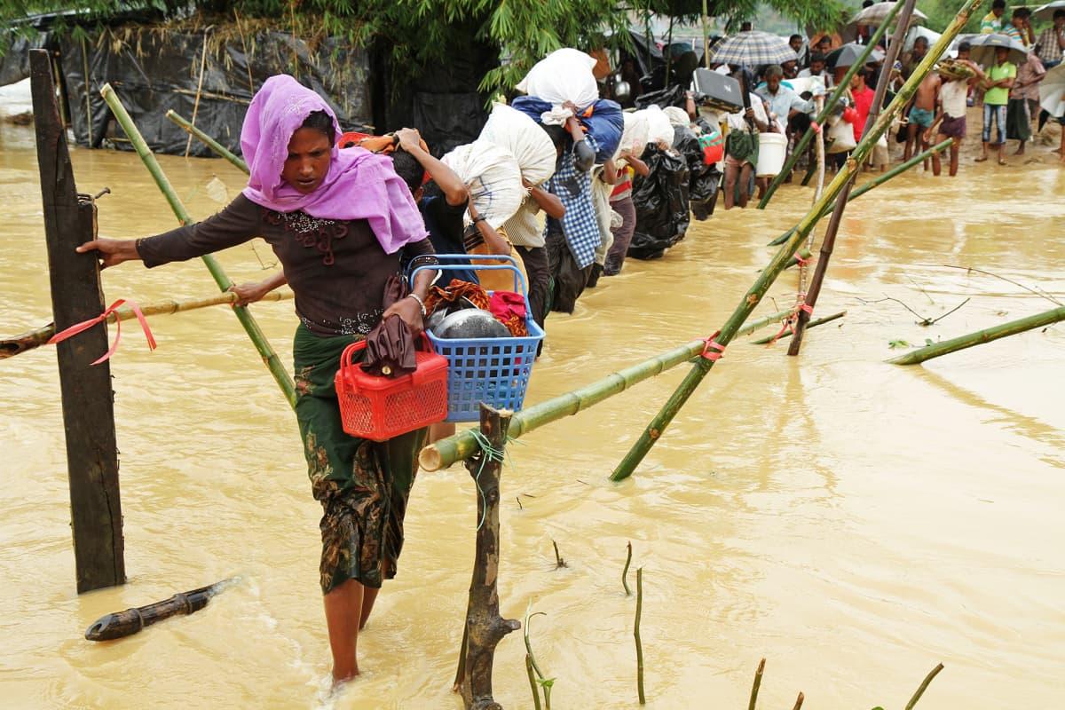 Pakolaisia tulvavedessä.