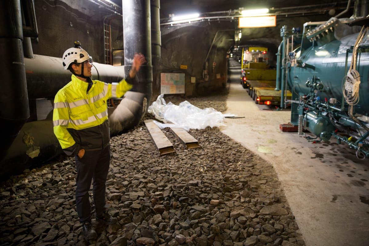 Eero Kaartokallio esittelee lämpöpumpun höyrystinosaa tunnelissa.