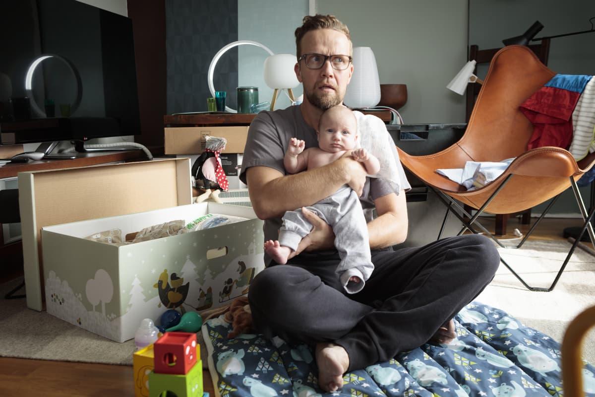 Mies pitää lasta sylissään.