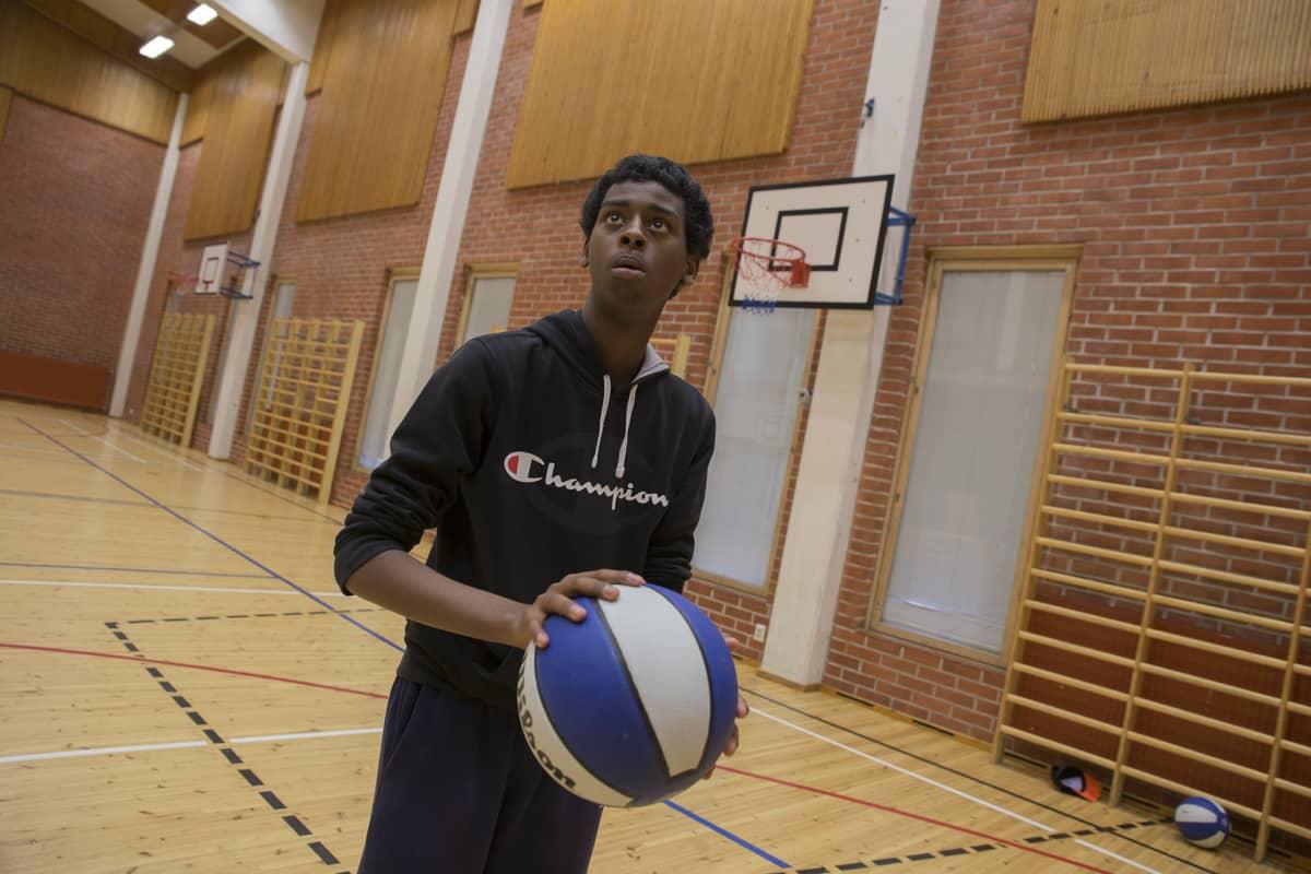 Nuori harrastamassa koripalloa.