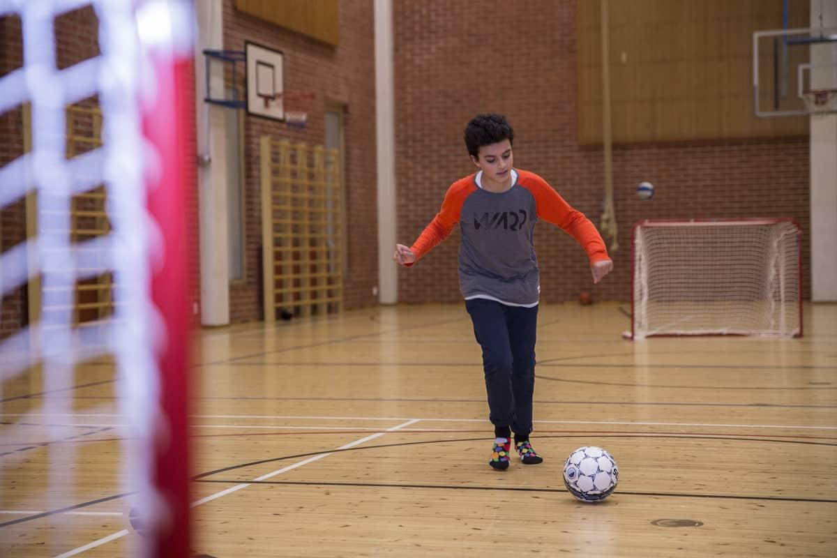 Nuori harrastamassa jalkapalloa.