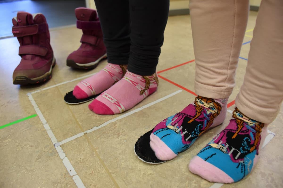 Lapset seisovat kengänpohjallisten päällä.